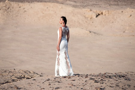 Bride young pretty woman brunette posing back in beautiful long white wedding bridal dress on background of sand desert