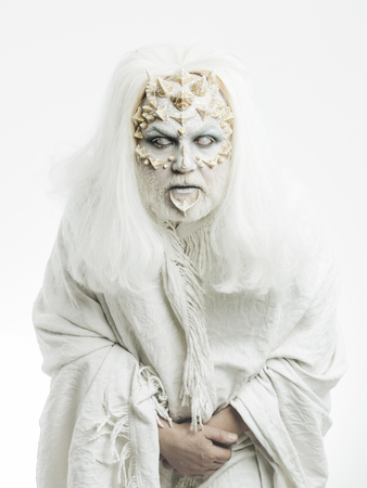 Demon with dragon skin and grey beard. Man with blind eyes on white background. Monster with thorns and warts on face. Wizard with long silver hair. Mystery and fantasy concept.
