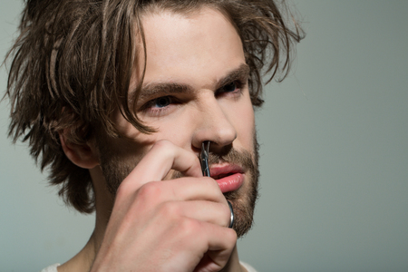 barber with long stylish hair. beauty and fashion. barbershop and hairdresser salon. man cut nose hair with scissors. Stock Photo