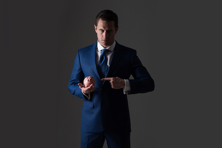 Elegante man. vertrouwen zaken man of succesvolle manager wijzend op spaarvarken in stijlvolle blauwe formele pak en stropdas op een grijze achtergrond. Zakelijk, bankieren, geld, spaarpot, krediet en spaargeld