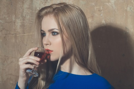 Girl drinking glass of red liqueur. Woman with blond long hair, make up in blue dress on beige wall. Alcohol, appetizer, bad habits, addictive and convive. Unhealthy lifestyle