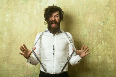 hair stylist: Hipster in shirt and suspenders. Guy or businessman at textured wall. Business fashion and beauty. Fashion model with stylish hair. Man with long beard and mustache on happy face. Stock Photo