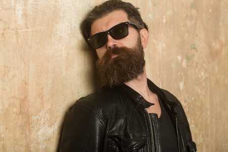 Man with long beard and mustache. Guy with serious face. Biker fashion and beauty. Fashion model on textured wall background. Hipster in leather jacket and glasses.