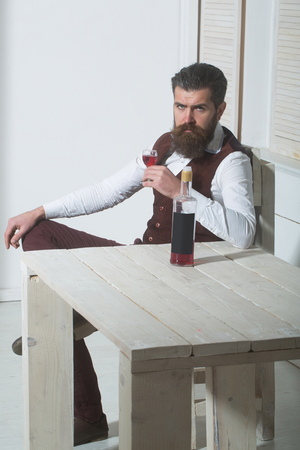 Hipster drinking red wine with bottle on wooden table. Brutal man with long beard and moustache indoors on white background. Alcohol and convive. Unhealthy lifestyle. Bad habits 版權商用圖片