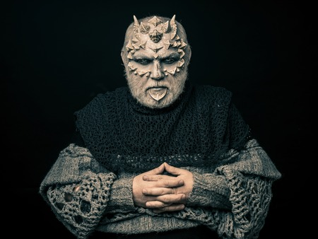 Demon with folded hands isolated on black. Alien or reptilian makeup with sharp thorns and warts. Horror and fantasy concept. Man with dragon skin and beard. Monster in grey knitted sweater.