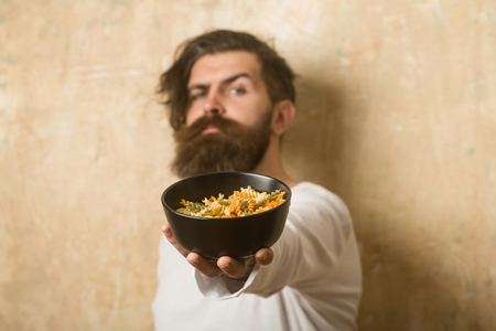 Cooking raw spaghetti in restaurant. Cook or chef bearded man with bowl. Man with pasta in hand. Hipster hold Italian macaroni. Healthy food and dieting. Stok Fotoğraf
