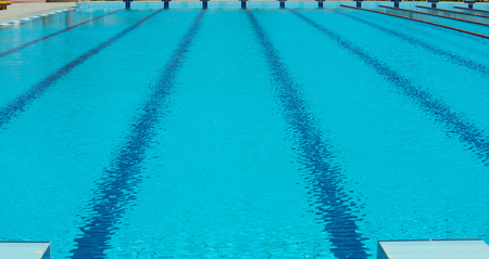 Pool for swimming with epmty lanes blue tarnsparent water and rope lines, sport race competition, fitness, training concept