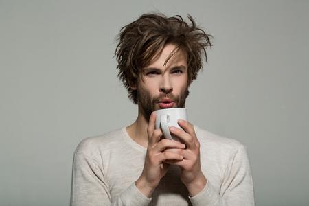 Le rafraîchissement du matin de l'homme avec une tasse de thé ou de café a mal mis les vêtements en sous-vêtements sur fond gris et buvez de l'énergie Banque d'images - 82482838