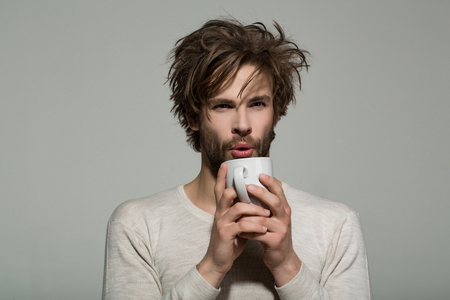 morning refreshment of man with cup of tea or coffee has uncombed hair in underwear on grey background, and drink, energy Stock fotó