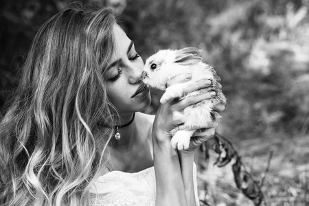 lapin sexy: Femme bisous joli petit lapin le jour d'été sur fond naturel, noir et blanc
