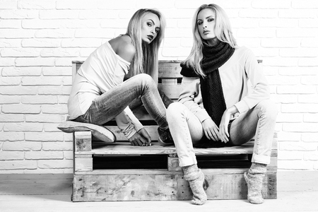 fashion model with blond hair in jeans and sweatshirt sits on wooden pallet sofa on white brick wall, black and white Reklamní fotografie
