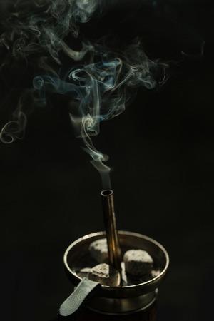 Fumar y adicción. Droga y relájate Carbón de leña de la cachimba en taza metálica con el instrumento del humo y de las pinzas o de las pinzas en fondo negro. Foto de archivo - 82576916