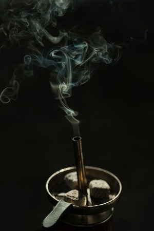 Smoking and addiction. Drug and relax. Hookah charcoal in metallic cup with smoke and tweezers or forceps tool on black background.