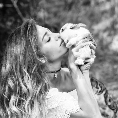 lapin sexy: Fille bisous joli petit lapin le jour d'été sur fond naturel, noir et blanc Banque d'images