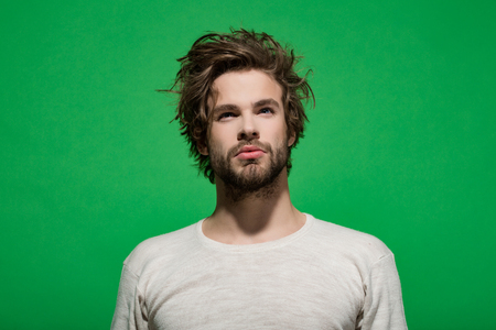 morning wake up of concentrated man with beard and long hair in white underwear on green background, barbershop