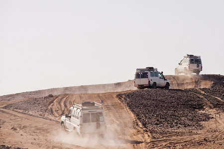 Vehicles bashing through desert hills on dusty sand road on white sky background.