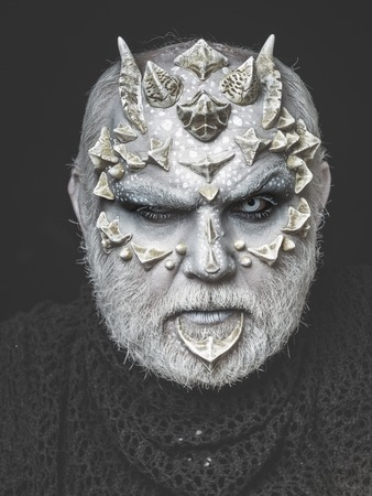 horror man or monster with horns or thorns on face with futuristic makeup of guy alien with beard and lens in eyes on black background