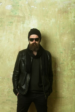 Man with long beard and mustache. Hipster in leather jacket and hat with glasses. Guy with serious face. Fashion model on textured wall background. Biker fashion and beauty.