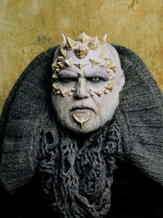 Monster face with white eyes, sharp thorns and warts. Alien or sorcerer makeup. Demon head with grey collar on abstract beige wall. Horror and fantasy concept. Man with dragon skin and beard.
