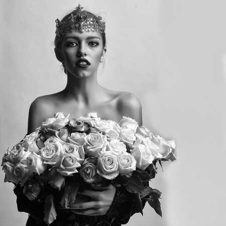 princess woman with luxury crown with diamond and gem has bare shoulders hold rose bouquet, black and white Stock Photo
