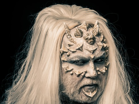 Alien or reptilian makeup. Man with dragon skin and beard. Demon head with grey hair isolated on black. Monster face with white eyes, sharp thorns and warts. Horror and fantasy concept.