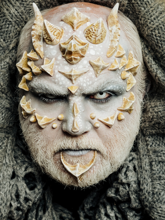 creepy alien: Monster face with white eyes, sharp thorns and warts. Man with dragon skin and beard. Alien or reptilian makeup. Demon head on grey knitted background. Horror and fantasy concept. Stock Photo