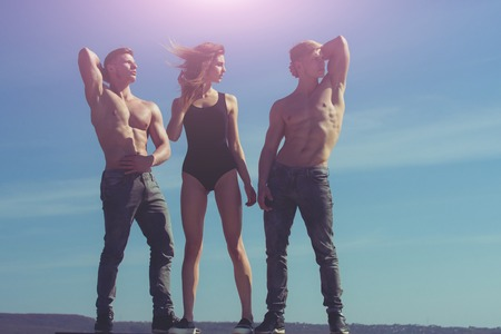 energy work: girl with athletic bodybuilder. Woman and twins with muscular body. workout and healthy fitness. Men and coach outdoor on blue sky. Sport people or team work.