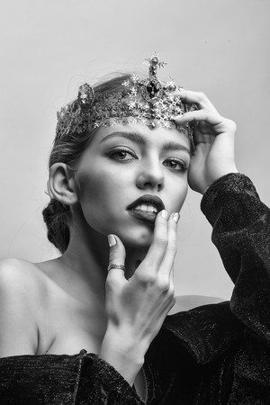 woman with luxury crown with diamond and gem has bare shoulders black and white