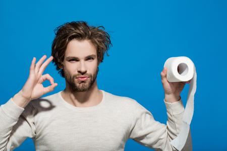 朝の ok のジェスチャーで下着で男。深刻な顔をもつ男は、トイレット ペーパーを保持します。不妊および純度。衛生と衛生。トイレ、お手洗い。