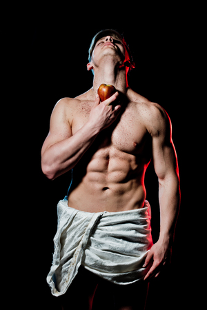 Gladiator or greek god. Athletic bodybuilder pose as statue. Man with muscular wet body in white fascia. Sport and workout. Adam with glitter on chest hold apple fruit.