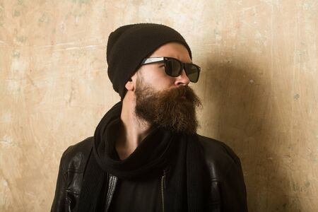 hair stylist: Man with long beard and mustache. Guy with serious face. Biker fashion and beauty. Fashion model on textured wall background. Hipster in leather jacket and hat with glasses.