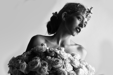 beauty with luxury crown with diamond and gem has bare shoulders hold rose bouquet, black and white Фото со стока