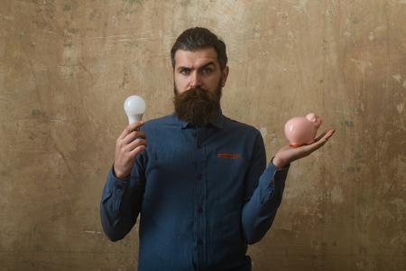 man met lange baard houd geld doos en lamp in de hand op beige achtergrond Stockfoto