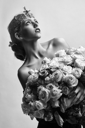 girl with luxury crown with diamond and gem has bare shoulders hold rose bouquet, black and white