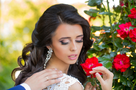 Beauty and fashion. Woman with dress and veil at red rose. Wedding holiday celebration. Girl with fashionable makeup in earring. Bride with long brunette hair with flower. Stock Photo