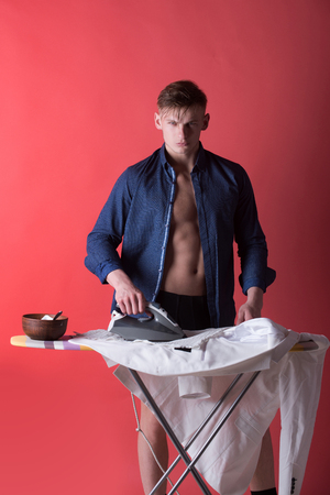 Athlete with muscular torso on red background. Bowl with food for healthy dieting on board. Housework and housekeeping concept. Man ironing clothes with iron. Macho in open blue shirt.