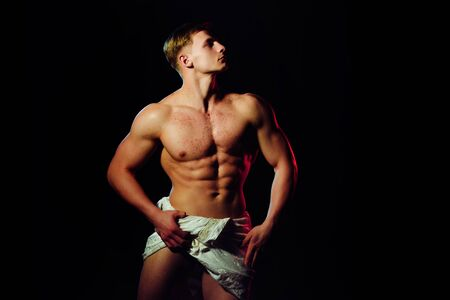 Man with muscular wet body in white fascia. Athletic bodybuilder pose as statue. Gladiator or greek god. Sport and workout. Adam with glitter on bare chest.