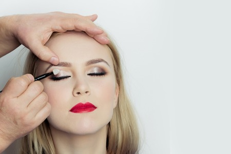 Girl with closed eyes and red lips getting makeup on eyelids. Male hand applying shiny eyeshadows on woman face with make up brush. Visage, cosmetics, skincare. Beauty salon, copy space Stock Photo