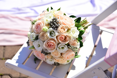 wedding bouquet of pink and white rose flower on wooden chair sunny summer outdoor