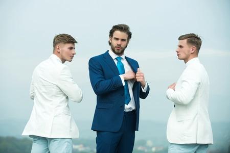 男性が青い空にポーズします。上司と晴れた日に従業員。フォーマルなスーツを身に着けているビジネス人々 のグループ。ボディー ガードを持つ実