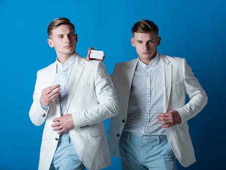 青色の背景空白のカードを保持している男性。銀行とコンセプトを保存します。白のジャケットを身に着けているビジネスマン。ビジネス コミュニ