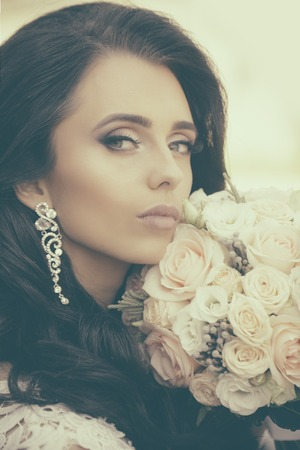 Woman with dress and veil at rose bouquet. Bride with long brunette hair with flower. Girl with fashionable makeup in earring. Wedding holiday celebration. Beauty and fashion.