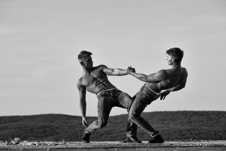 Twin men or bodybuilders, athletes with sexy, muscular torsos with six packs, abs, biceps, triceps wrestling outdoor in mountains on sky, black and white Stock Photo