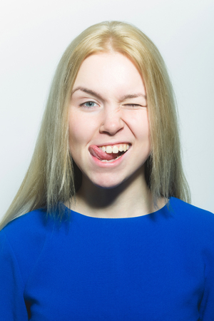winking woman with white teeth on cute face show tongue isolated on white. Woman with young healthy skin and no makeup. Fashionable model with long blond hair in blue dress. Beauty salon. Stomatology Stock Photo