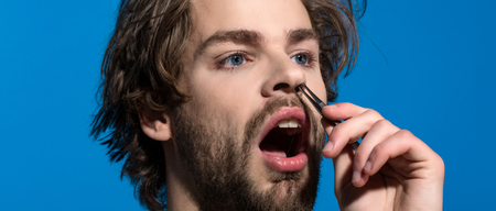 beauty and fashion. barbershop and hairdresser salon. man twitch nose hair with tweezers. barber with long stylish hair. Stock Photo - 83380538