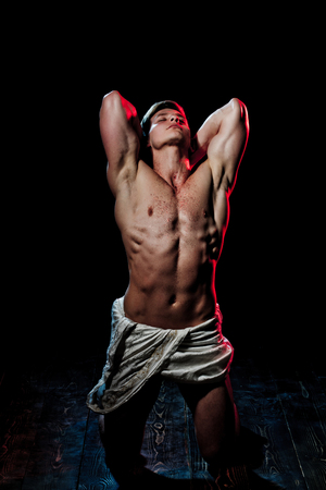 Gladiator or greek god. Sport and workout. Adam with glitter on bare chest. Man with muscular wet body in white fascia. Athletic bodybuilder pose as statue.