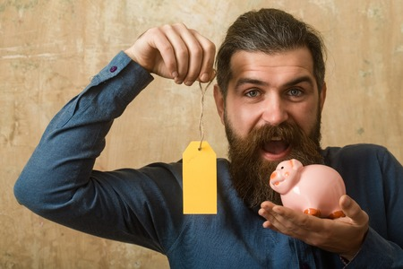 Businessman take bank credit. Loan and bankruptcy. Man with beard on happy face. Money and success. Guy hold shopping tag and moneybox.