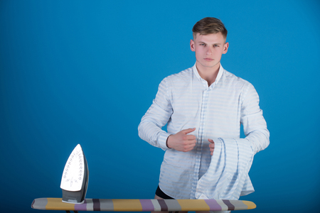 Macho wearing striped shirt. Housework and fashion concept. Man with laundry for ironing. Model using iron. Ironing board on blue background. Stock Photo