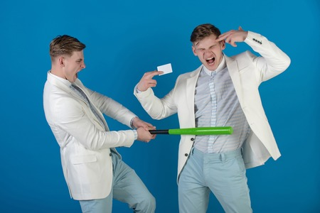 Managers shouting and fighting on blue background. Man showing finger gun with blank card. Businessman batting rival with baseball bat. By force or persuasion. Business negotiations concept. Stock Photo