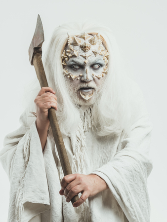 Wizard with long silver hair. Demon with axe in hands on white background. Monster with thorns and beard on face. Man with blind eyes. Horror and death concept.